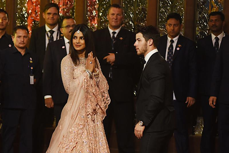 "Newlyweds Indian Bollywood actress Priyanka Chopra (L) and US musician Nick Jonas attend the wedding ceremony of Indian businesswoman Isha Ambani with Indian business men Anand Piramal in Mumbai on December 12, 2018. - Topping anything in hit film ""Crazy Rich Asians"", the only daughter of India's richest man ties the knot on December 12 after days of lavish celebrations that included a Beyonce concert in a lakeside palace. Isha Ambani, whose father is tycoon Mukesh Ambani, was set to wed Anand Piramal, son of Indian billionaire industrialist Ajay Piramal, in the Ambanis' 27-storey home in Mumbai. (Photo by Sujit Jaiswal / AFP) (Photo credit should read SUJIT JAISWAL/AFP/Getty Images)"