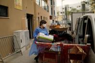 A woman carries goods collected on the Faro Food Bank Against Hunger to a truck, during the coronavirus disease (COVID-19) pandemic in Faro