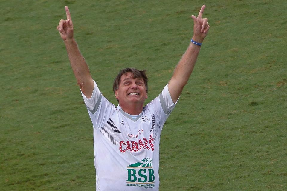 "Brazilian President Jair Bolsonaro celebrates after scoring a goal during the ""Natal sem Fome"" (Christmas without Hunger) charity football match at Vila Belmiro stadium in Santos, Sao Paulo state, Brazil, on December 28, 2020. (Photo by Miguel SCHINCARIOL / AFP) (Photo by MIGUEL SCHINCARIOL/AFP via Getty Images)"