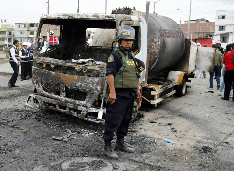 A police officer stands by the wreckage of a gas tanker that exploded in Lima, killing at least eight people and leaving dozens injured