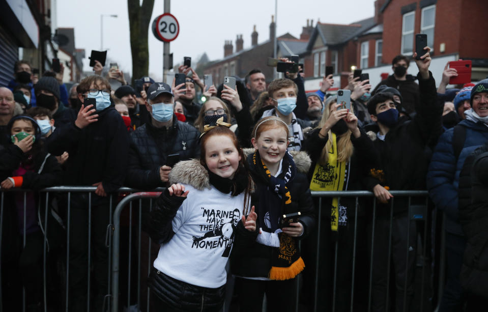Marine fans wait for the players to arrive for the English FA Cup third round soccer match between Marine and Tottenham Hotspur at Rossett Park stadium in Crosby, Liverpool, Sunday, Jan. 10, 2021. (Clive Brunskill/Pool via AP)