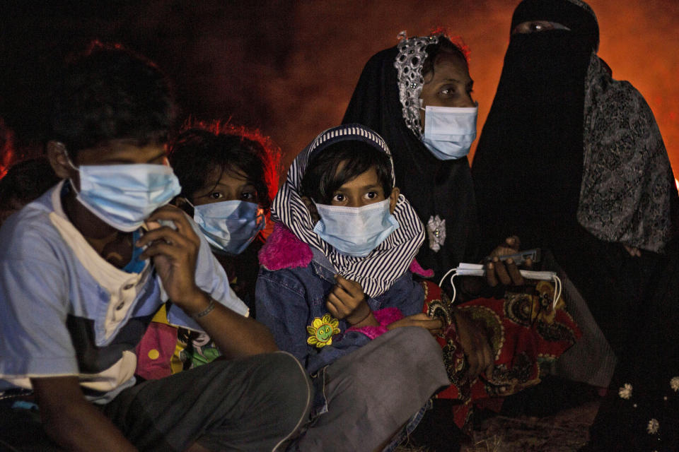 Ethnic Rohingya women and children sit by a fire on a beach after their boat was stranded on Idaman Island in East Aceh, Indonesia, late Friday, June 4, 2021. Villagers in Indonesia's Aceh province discovered a stranded boat Friday carrying dozens of Rohingya Muslims, including children, who had left a refugee camp in Bangladesh, officials said. (AP Photo/Zik Maulana)