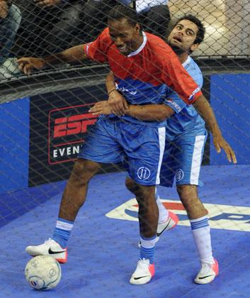 Indian cricketer Virat Kholi (R) puts his arms around International football player, from the Ivory Coast, Didier Drogba (L) while they play an exhibition match in New Delhi on June 17, 2012. Drogba is in the city for the grand finale of the Pepsi T20 football tournament.  AFP PHOTO/ SAJJAD HUSSAIN