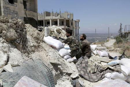 Rebel fighters from the Ahrar al-Sham Islamic Movement take positions behind sandbags in Jabal al-Arbaeen, which overlooks the northern town of Ariha, one of the last government strongholds in the Idlib province May 26, 2015. REUTERS/Khalil Ashawi