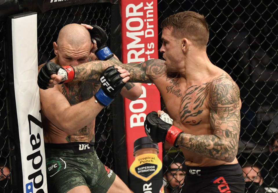 Dustin Poirier (left) punches Conor McGregor of Ireland in a lightweight fight during the UFC 257 event inside Etihad Arena in Abu Dhabi.