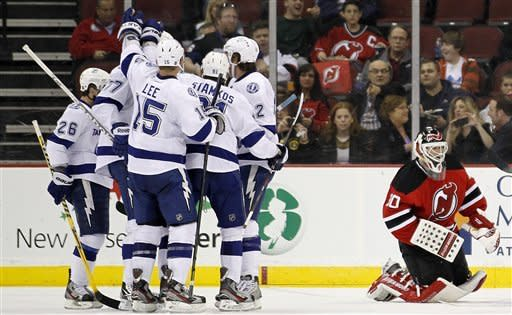 New Jersey Devils goalie Martin Brodeur kneels near his goal as members of the Tampa Bay Lightning celebrate a goal scored by Ryan Malone in the second period of an NHL hockey game, Thursday, March 29, 2012, in Newark, N.J. (AP Photo/Julio Cortez)