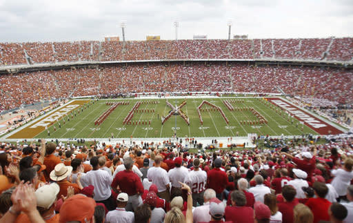 FILE- In this Oct. 8, 2011, file photo, Texas fans, left, and Oklahoma fans, right, fill the Cotton Bowl for the NCAA college football game between Oklahoma and Texas in Dallas. No. 5 Oklahoma and No. 9 Texas are playing in a rare Red River rivalry rematch in the Big 12 championship game on Saturday. It is the first time in 115 years that the border state rivals will play twice in the same season. (AP Photo/Mike Fuentes, File)