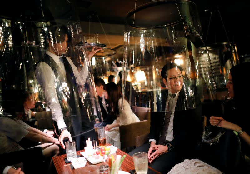 Goldfish bowl-like acrylic screens are seen installed as part of new social distancing measures and prevention of infection against the coronavirus disease (COVID-19), are installed at a night club in Tokyo