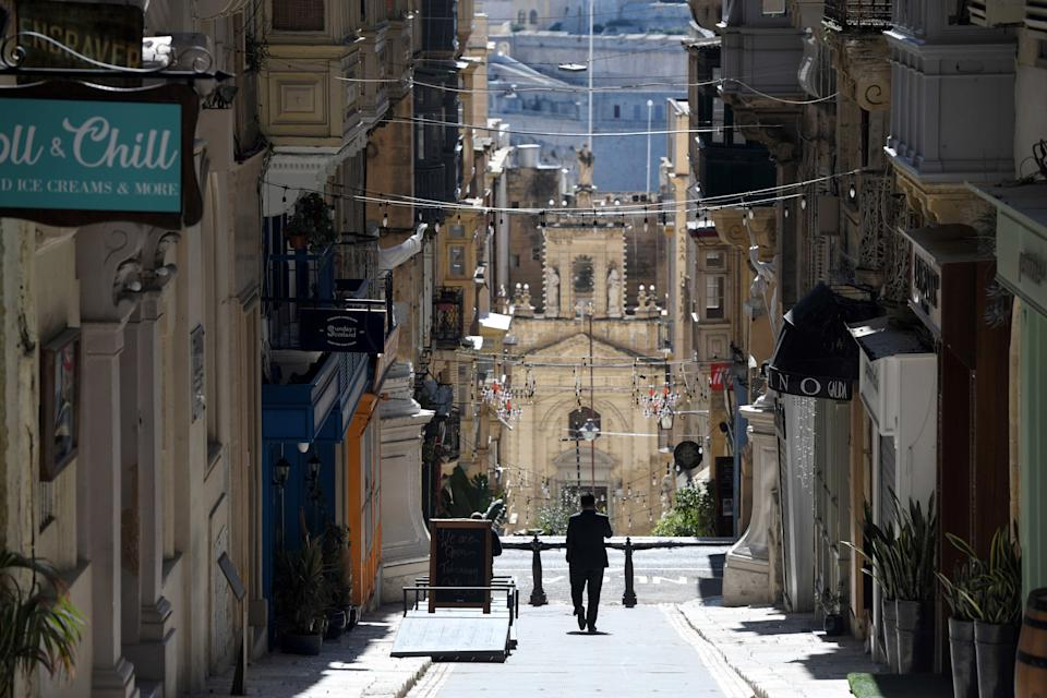 VALLETTA, March 11, 2021 -- A man walks on an empty street in Valletta, Malta, March 11, 2021. The Maltese government on Wednesday announced the closure of schools and non-essential shops in response to a spike in new COVID-19 cases, almost two-thirds of which are attributable to the variant first reported in the UK. The new measures, which will be in force until April 11, include the closure of all non-essential shops and those providing non-essential services such as hairdressers and beauticians while the limitation of group gatherings in public down to a maximum of four people. (Photo by Jonathan Borg/Xinhua via Getty) (Xinhua/Jonathan Borg via Getty Images)