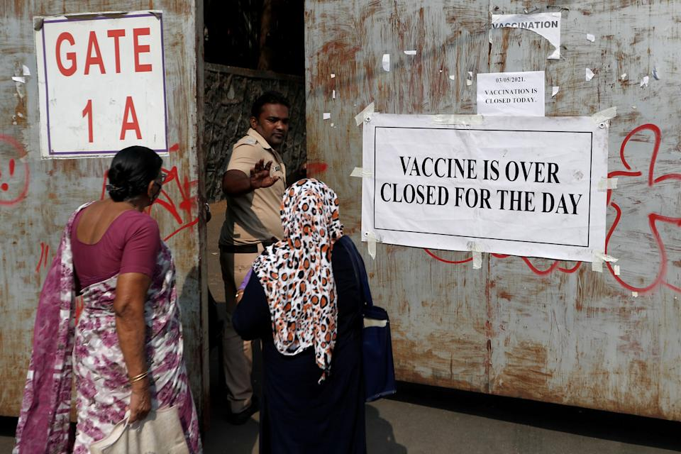 A policeman asks people who came to receive a dose of a coronavirus disease (COVID-19) vaccine to leave as they stand outside the gate of a vaccination centre which was closed due to unavailability of the supply of COVID-19 vaccine, in Mumbai, India, May 3, 2021. REUTERS/Francis Mascarenhas     TPX IMAGES OF THE DAY