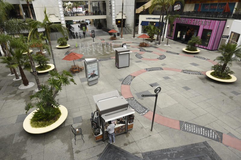 A vendor waits for customers in a sparsely populated courtyard at the Hollywood & Highland shopping and entertainment complex, Thursday, March 12, 2020, in the Hollywood section of Los Angeles. (AP Photo/Chris Pizzello)