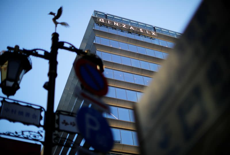 The signage of Ginza Six, a luxury shopping complex, is seen through street signs, in Tokyo
