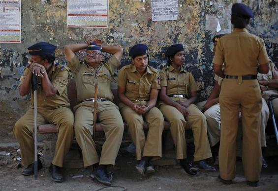 Policemen keep watch during a protest rally organized by various trade unions in Mumbai, February 28, 2012.