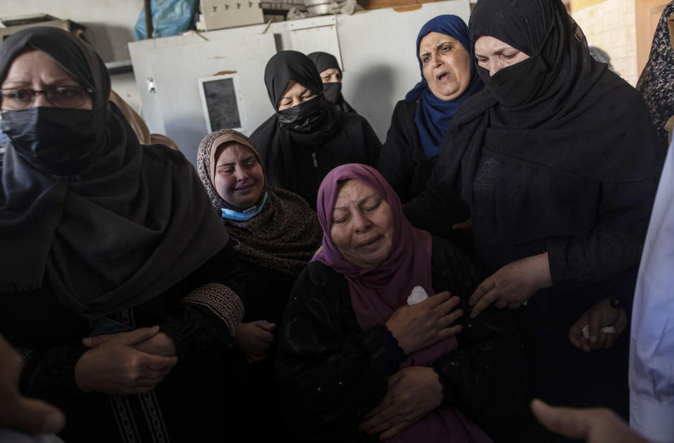 Palestinian relatives mourn over the bodies of four brothers from the Tanani family who were found under the rubble of a destroyed house following Israeli airstrikes in Beit Lahiya, northern Gaza Strip, Friday, May 14, 2021. (AP Photo/Khalil Hamra)