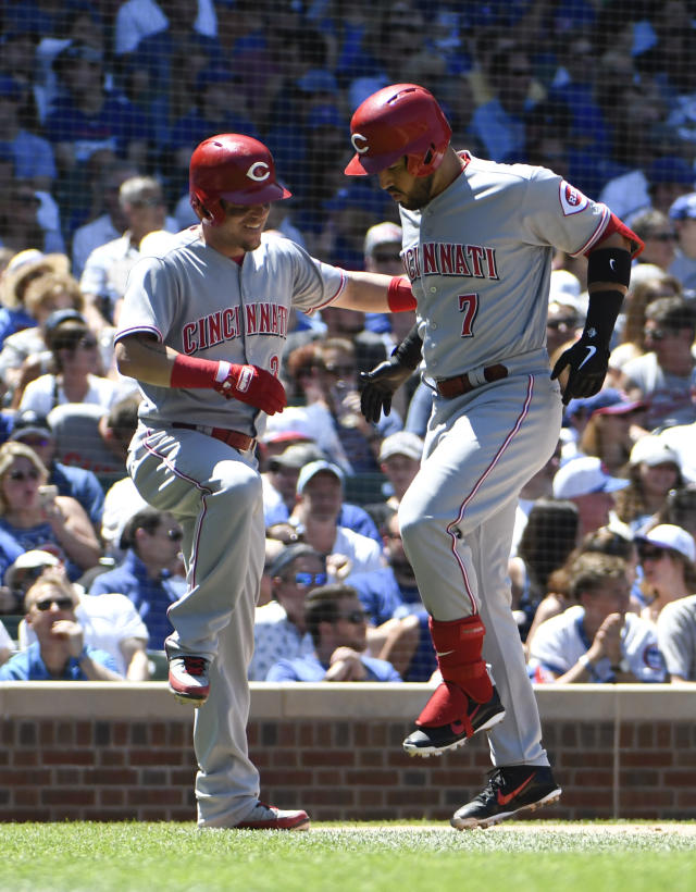 Cincinnati Reds' Eugenio Suarez (7) is greeted by Scooter Gennett, left, after hitting a three-run home run against the Chicago Cubs in the third inning of a baseball game Saturday, July 7, 2018, in Chicago. (AP Photo/David Banks)
