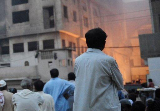 <p>Anxious relatives and local residents watch the rescue operation at a garment factory in Karachi on Wednesday. A huge fire at a garment factory in Pakistan's largest city of Karachi has killed at least 240 people, Karachi city's police chief Iqbal Mehmood, told AFP.</p>