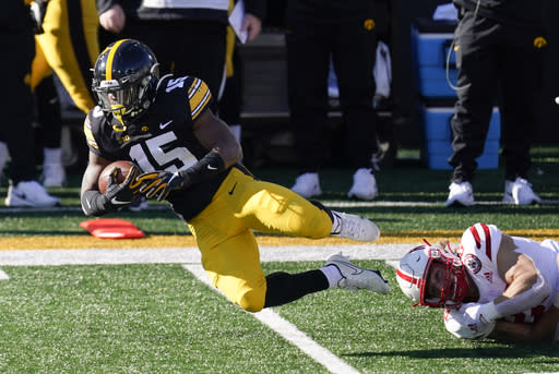 Iowa running back Tyler Goodson (15) is tackled by Nebraska linebacker Luke Reimer, right, during the first half of an NCAA college football game, Friday, Nov. 27, 2020, in Iowa City, Iowa. (AP Photo/Charlie Neibergall)