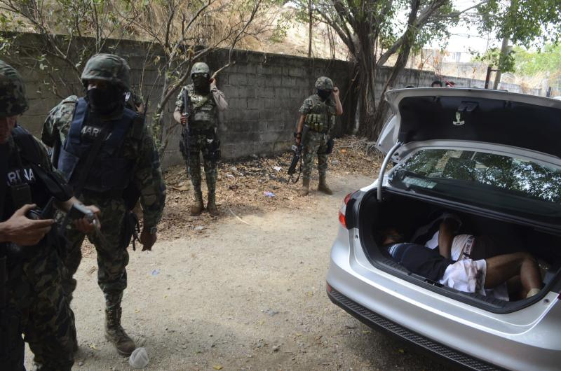 Mexican navy marines inspect a car that was found with the bodies of two men inside the trunk in the Pacific resort city of Acapulco, Mexico Wednesday May 23, 2012. A message to a rival gang was left next to the car. (AP Photo/Bernandino Hernandez)