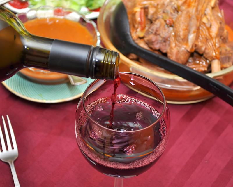 TORONTO, ONTARIO, CANADA - 2010/12/26: Close up of red wine pouring into a wine glass. Different food is on the table in the blurred background. (Photo by Roberto Machado Noa/LightRocket via Getty Images)