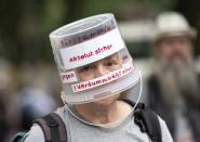 A demonstrator walks through Berlin-Charlottenburg with a plastic bucket placed on his head reading 'Absolutely safe against the stupidity virus', in Berlin, Sunday Aug. 1, 2021, during a protest against coronavirus restrictions. Hundreds have turned out in Berlin to protest the German government's anti-coronavirus measures despite a ban on the gatherings, leading to arrests and clashes with police. (Fabian Sommer/dpa via AP)