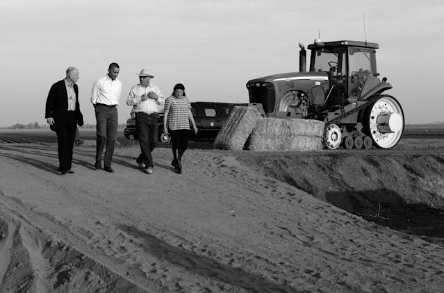 President Barack Obama walks with farmers Joe Del Bosque and Maria Del Bosque as he tours a farm affected by drought in Los Banos, Calif., on Feb. 14, 2014. California Gov. Jerry Brown is at left. (Photo: Kevin Lamarque/Reuters)