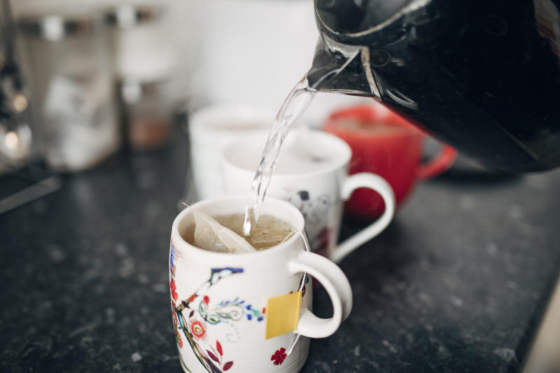 A photo of hot water being poured from a kettle into a mug in a kitchen.