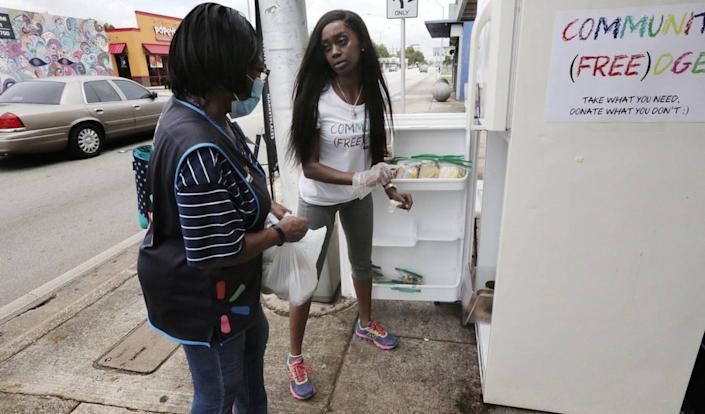 Sherina Jones, center, passes out food from the community refrigerator she set up to feed locals who may be struggling due to the pandemic.