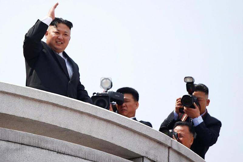 Leader: Kim Jong Un waves to people attending a military parade marking the 105th birth anniversary of country's founding father Kim Il Sung (REUTERS)