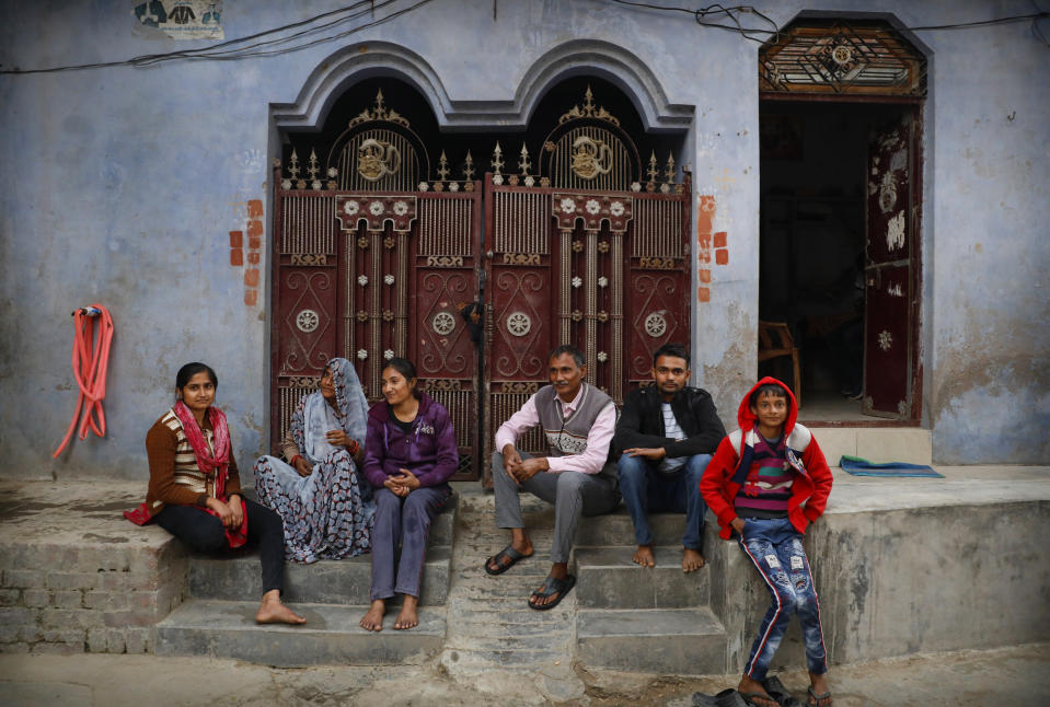 Indian farmer Ram Singh Patel, third right, poses for a photograph with his wife Kantee Devi, second left, and children Anuradha Patel, left, Asmita Patel, third left, Shubham Patel, second right, and Shivansh Patel outside their village house in Fatehpur district, 180 kilometers (112 miles) south of Lucknow, India, Saturday, Dec. 19, 2020. Patel's day starts at 6 in the morning, when he walks into his farmland tucked next to a railway line. For hours he toils on the farm, where he grows chili peppers, onions, garlic, tomatoes and papayas. Sometimes his wife, two sons and two daughters join him to lend a helping hand or have lunch with him. (AP Photo/Rajesh Kumar Singh)