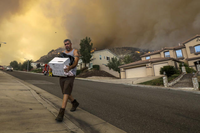 <p>Manuel Trujillo packs his belongings as flames of Holy Fire came very close to his home on 29000 block of Sandpiper Drive in Lake Elsinore, Calif., on Aug. 9, 2018. (Photo: Irfan Khan/Los Angeles Times via Getty Images) </p>