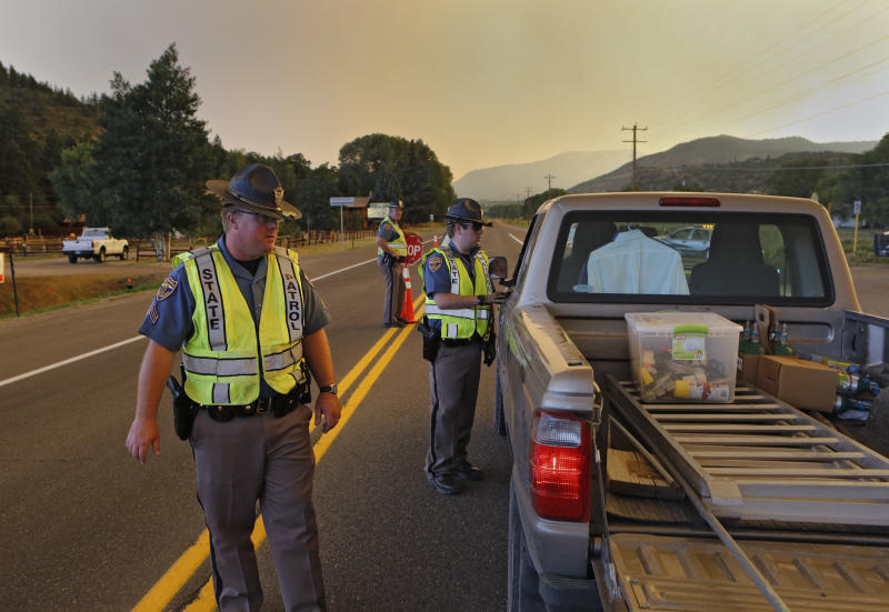 Colorado State Patrol officers man a road block on U.S. 160 east of South Fork, Colo., on Friday evening June 21, 2013. The highway was closed through South Fork and over Wolf Creek Pass because of a wildfire burning west of the town. (AP Photo/Ed Andrieski)