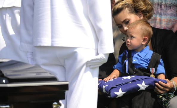 The U.S. Navy Color Guard presents the flag that adorned the casket of Jonathan Blunk to his son Maximus Blunk, 2, sitting on the lap of his mother Chantel Blunk at Mountain View Cemetery August 03, 2012, in Reno, Nevada. Blunk, a five-year U.S. Navy veteran, was killed in the July 20 shooting rampage at a movie theater in Aurora Colorado. (Photo by RJ Sangosti-Pool/Getty Images)
