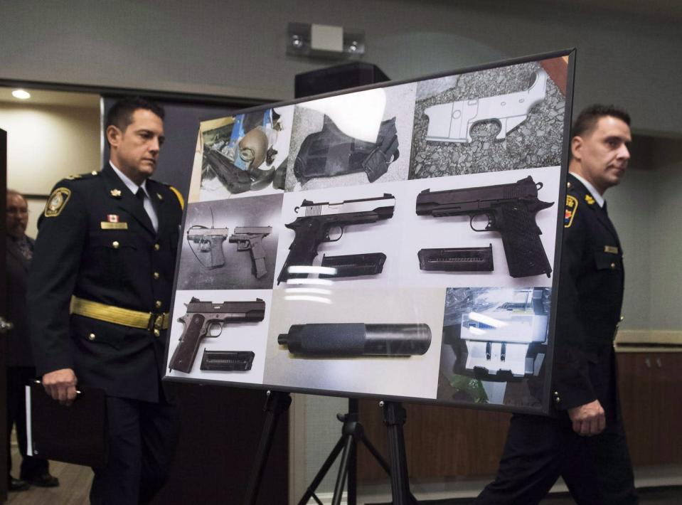 Police officers carry a billboard featuring photos of seized illegal firearms.