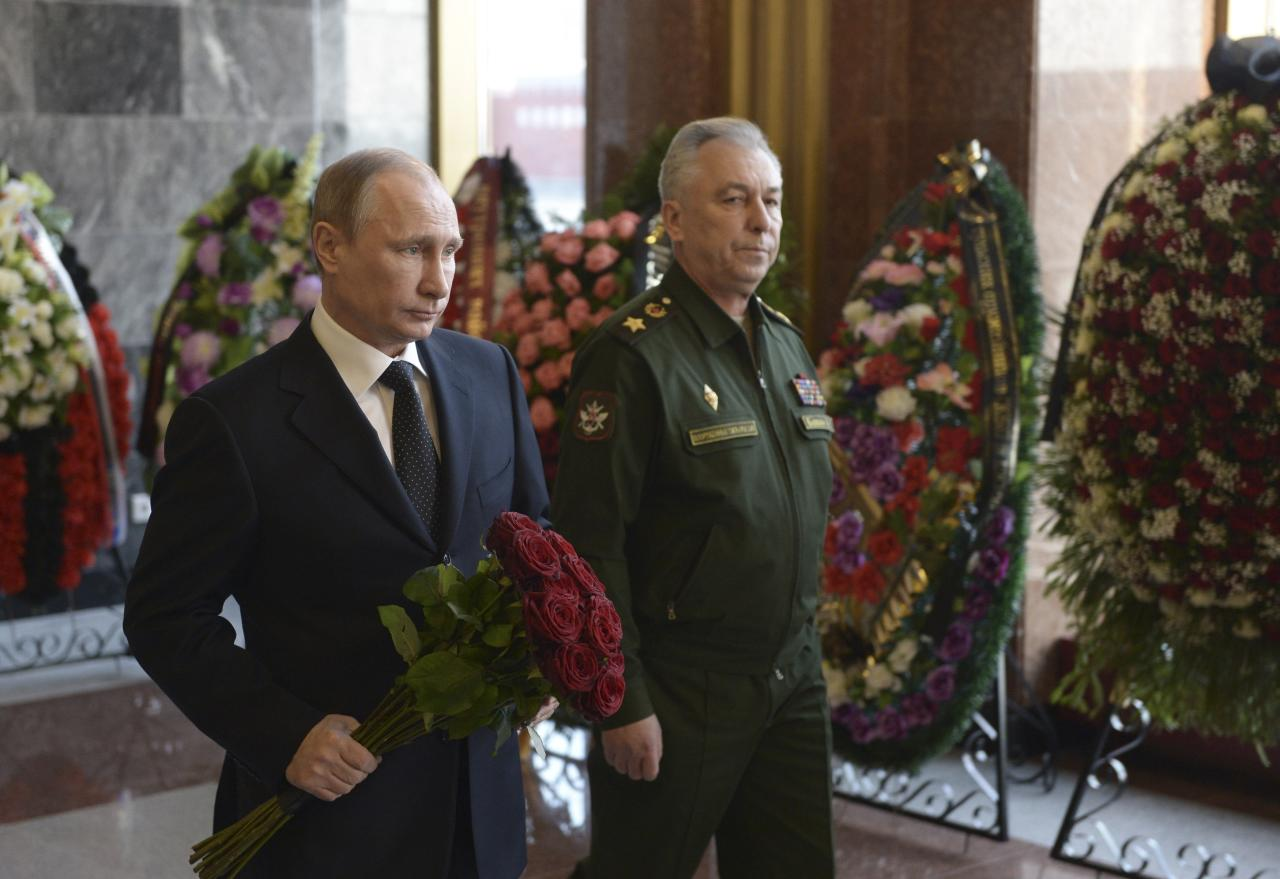 Russian President Vladimir Putin (L) pays respects to Mikhail Kalashnikov, chief designer of Izhmash Concern, a Russian firearms producer, during a commemoration ceremony in Mytischi outside Moscow, December 27, 2013. Russia buries assault rifle designer Kalashnikov on Friday. Kalashnikov, the designer of the assault rifle that has killed more people than any other firearm in the world, died on December 23, 2013, at 94. REUTERS/Alexei Nikolskyi/RIA Novosti/Kremlin (RUSSIA - Tags: OBITUARY POLITICS MILITARY) ATTENTION EDITORS - THIS IMAGE HAS BEEN SUPPLIED BY A THIRD PARTY. IT IS DISTRIBUTED, EXACTLY AS RECEIVED BY REUTERS, AS A SERVICE TO CLIENTS