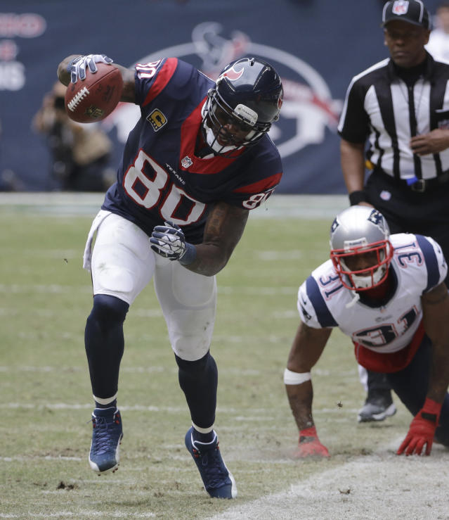 Houston Texans' Andre Johnson (80) works to stay inbounds after making a catch as New England Patriots' Aqib Talib (31) looks on during the third quarter of an NFL football game Sunday, Dec. 1, 2013, in Houston. (AP Photo/David J. Phillip)