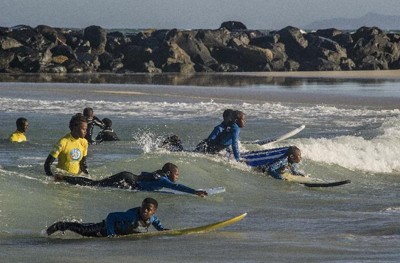 Waves for Change coaches (in yellow) show children the basics of surfing in the shallows of Monwabisi Beach, Khayelitsha, on August 7, 2014