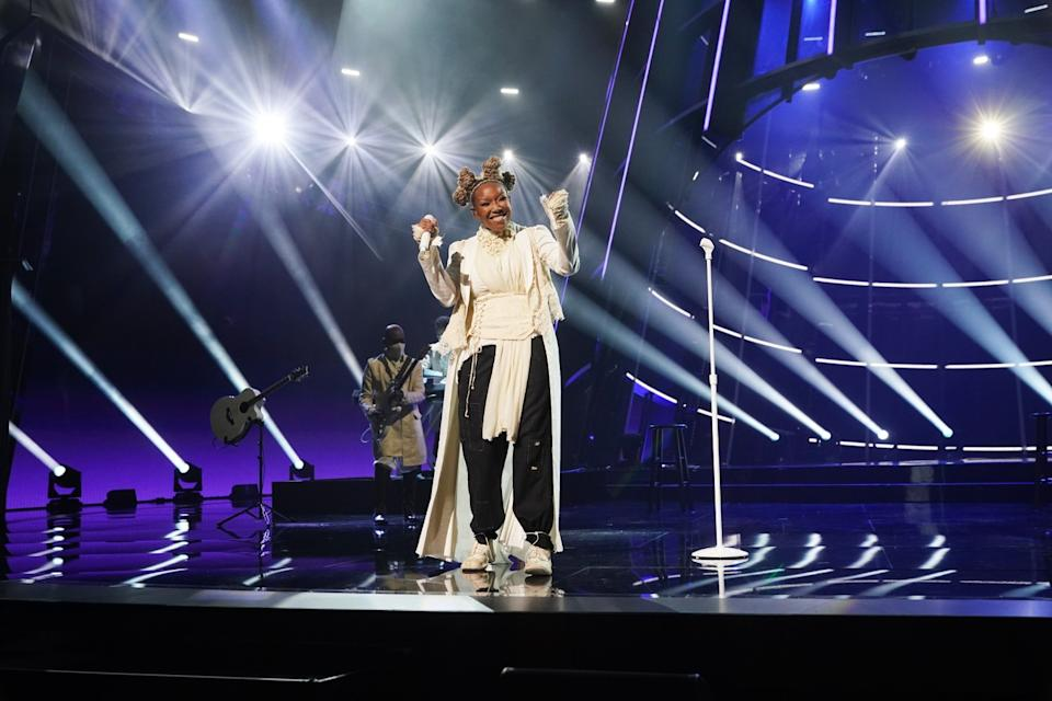 Brandy performs in lacey white shirt and black harem pants.