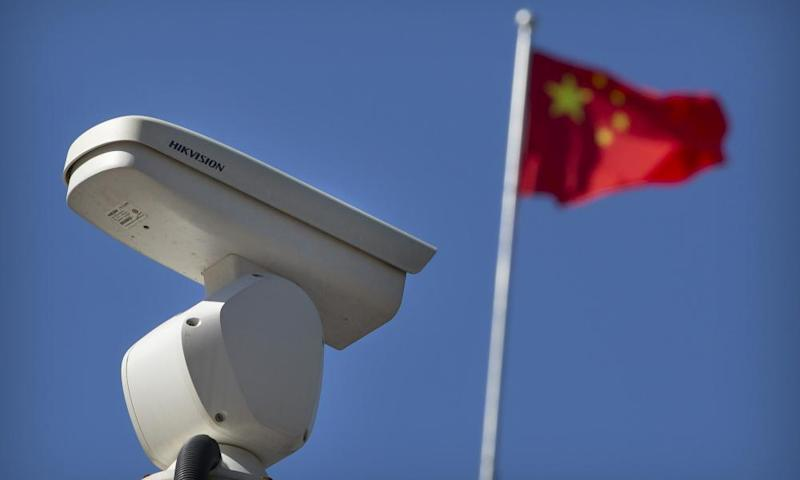 A Chinese flag flies near a security camera monitoring a traffic intersection in Beijing.