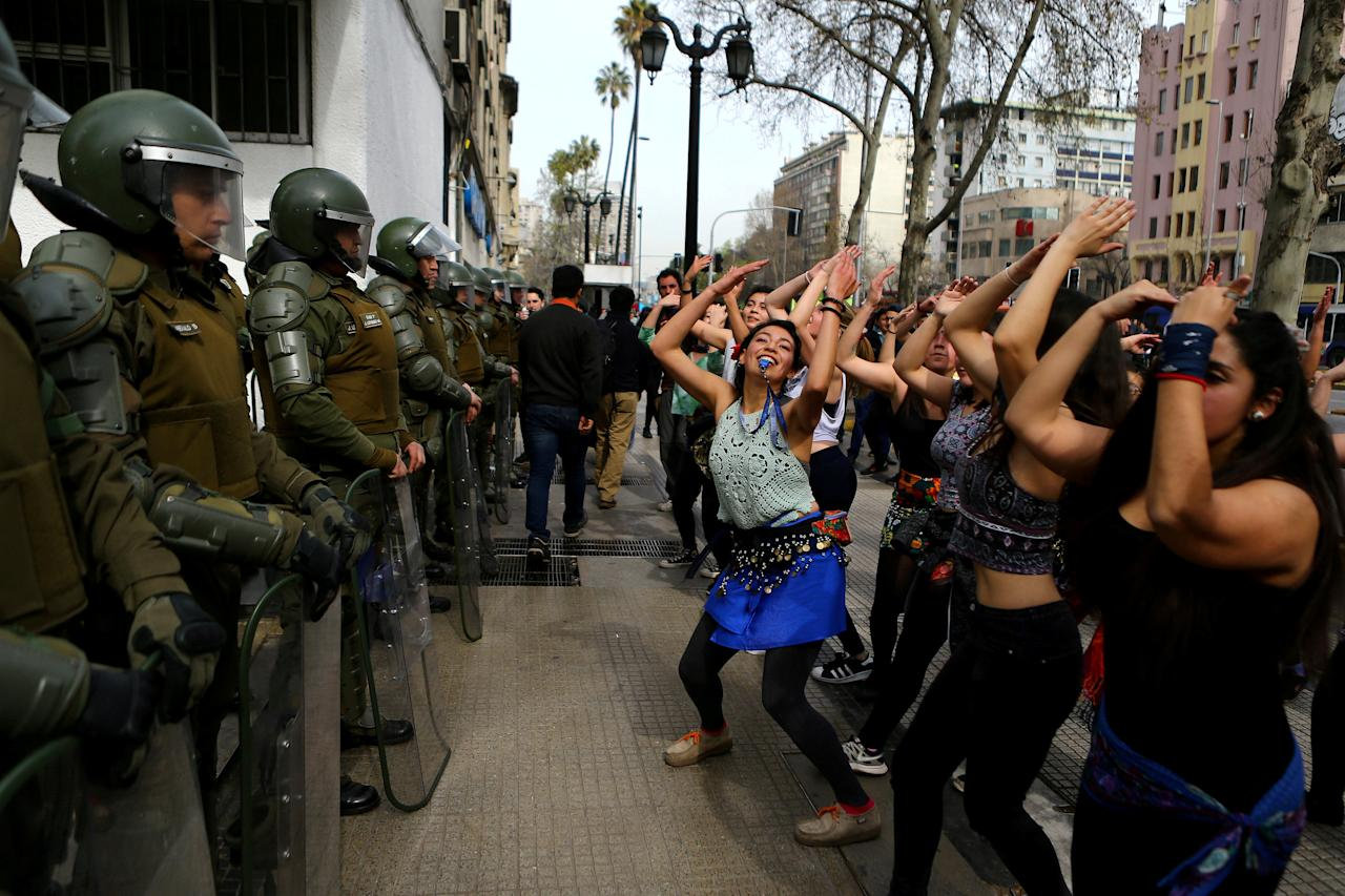 Demonstrators perform a dance in front of riot policemen during a march called by students to request changes in the education system in Santiago, Chile September 5, 2017. REUTERS/Ivan Alvarado     TPX IMAGES OF THE DAY