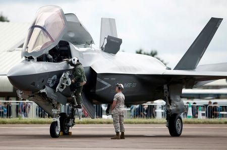 A pilot climbs down from the cockpit of a US Marine Corps Lockheed Martin F-35B fighter jet at the Royal International Air Tattoo at Fairford