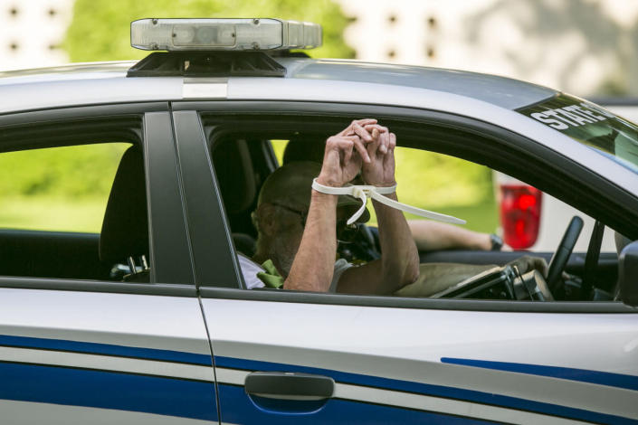 <p>An arrested protestor is taken away in a police car after failing to leave the scene outside the North Carolina state legislative building as people voiced their concerns about House Bill 2 in Raleigh, N.C., on May 16, 2016.<i> (Al Drago/CQ Roll Call/Getty Images)</i></p>