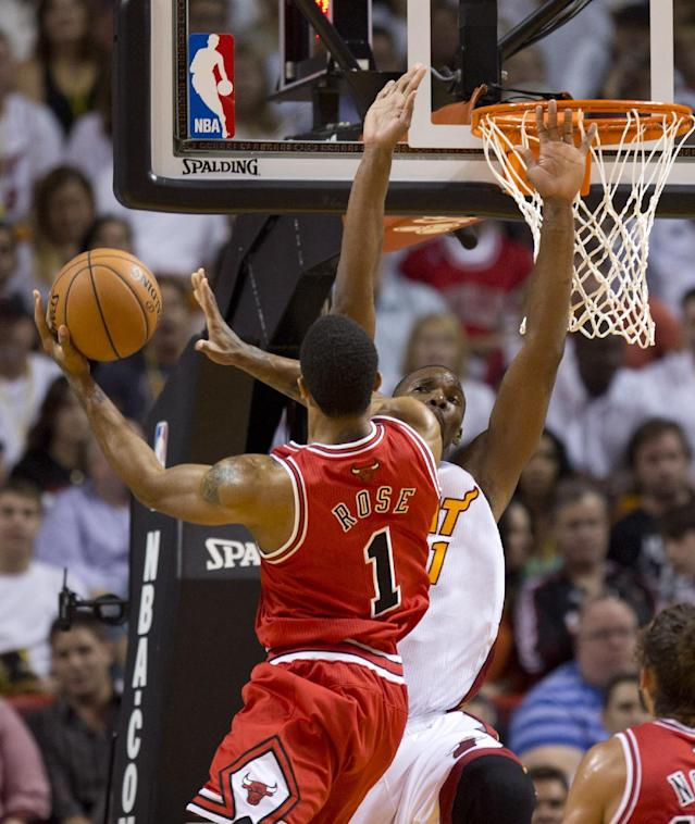 Chicago Bulls' Derrick Rose (1) slides past Miami Heat's Chris Bosh (1) for two points during the first half of an NBA basketball game in Miami, Tuesday, Oct. 29, 2013. (AP Photo/J Pat Carter)