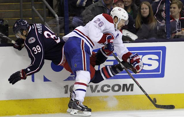 Montreal Canadiens' Josh Gorges, right, checks Columbus Blue Jackets' Michael Chaput during the second period of an NHL hockey game Friday, Nov. 15, 2013, in Columbus, Ohio. (AP Photo/Jay LaPrete)