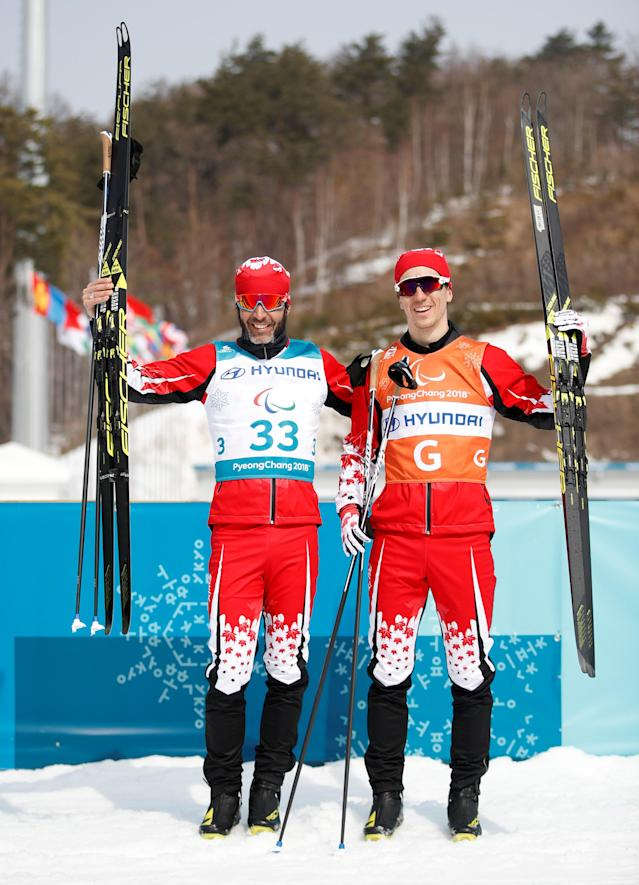 Cross-Country Skiing - Pyeongchang 2018 Winter Paralympics - Men's 20km Free - Visually Impaired - Alpensia Biathlon Centre - Pyeongchang, South Korea - March 12, 2018 - Brian Mckeever of Canada and his guide celebrates winning gold. REUTERS/Carl Recine