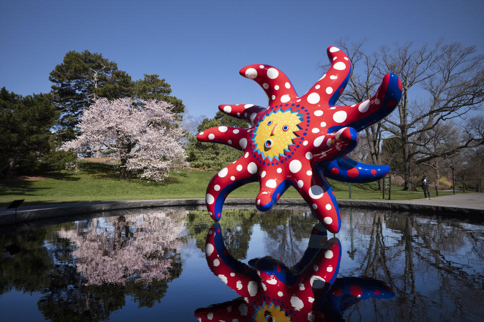 """The sculpture """"I Want to Fly to the Universe"""" by Japanese artist Yayoi Kusama is reflected in a pool at the New York Botanical Garden, Thursday, April 8, 2021 in the Bronx borough of New York. The expansive exhibit has opened, and ticket sales have been brisk in a pandemic-weary city hungry for more outdoor cultural events. (AP Photo/Mark Lennihan)"""
