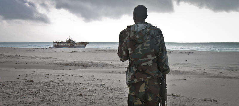 FILE - In this Sunday, Sept. 23, 2012 file photo, a Somali soldier looks out at a Taiwanese fishing vessel that washed up on shore after the pirates were paid a ransom and released the crew, in the once-bustling pirate den of Hobyo, Somalia. World sea piracy fell for a third straight year in 2013, as Somali pirates were curbed by international naval patrols and improved ship vigilance, an international maritime watchdog said Wednesday, Jan. 15, 2014. (AP Photo/Farah Abdi Warsameh, File)
