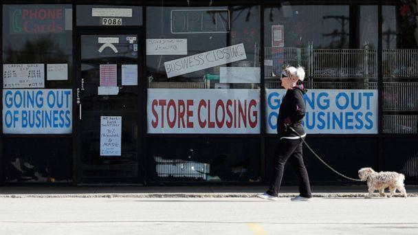 PHOTO: A woman takes walk with a dog in front of the closing signs displayed in a store's window front in Niles, Ill., May 13, 2020. (Nam Y. Huh/AP)