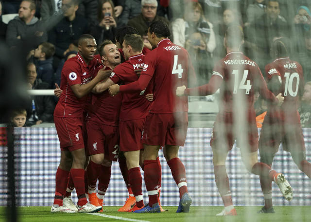 Liverpool players celebrate after Divock Origi, obscured, scored their third goal against Newcastle United during the Premier League soccer match at St James' Park, in Newcastle, England, Saturday May 4, 2019. (Owen Humphreys/PA via AP)