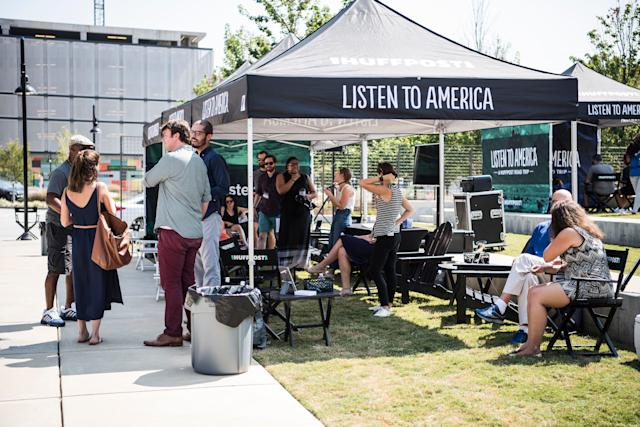 HuffPost employees talk with visitors to the Listen to America tents.
