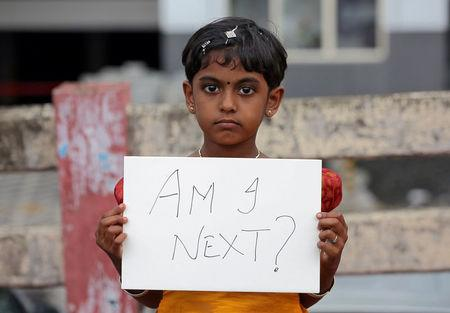 A gild holds a placard during a protest against the rape of an eight-year-old girl in Kathua, near Jammu, in Kochi, India April 15, 2018. REUTERS/Sivaram V